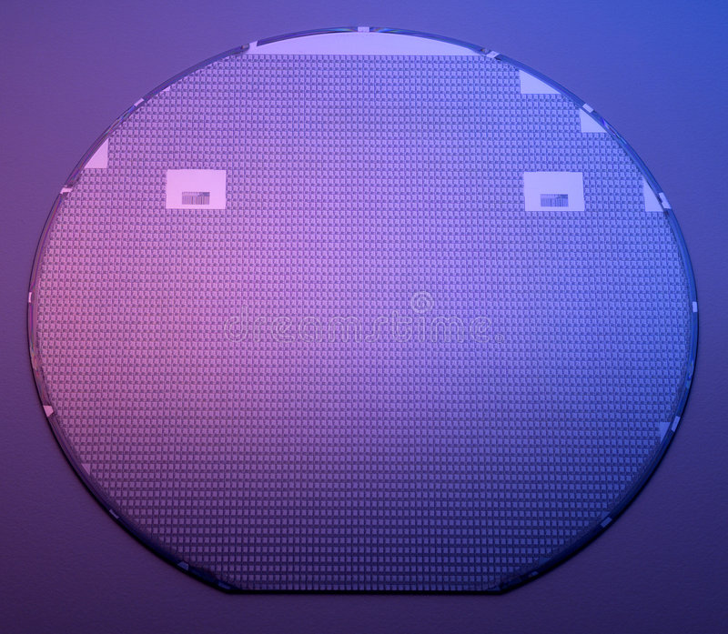 Silicon wafer. Big silicon wafer on formica background lit by a blue and magenta light source