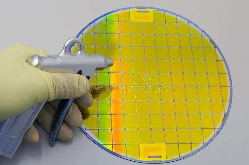 Silicon Wafer cleaning by nitrogen from gun for cleanroom in the hands by gloves - A wafer is a thin slice of semiconductor. Material, such as a crystalline stock image