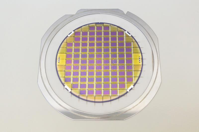 Silicon wafer with microchips fixed in the holder with steel frame on the grey background and ready for process. Silicon Wafers with microchips - used in stock image