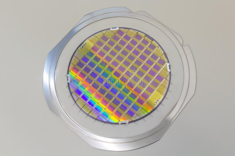 Silicon wafer with microchips fixed in the holder with steel frame on the grey background and ready for process. Silicon Wafers with microchips - used in stock photo