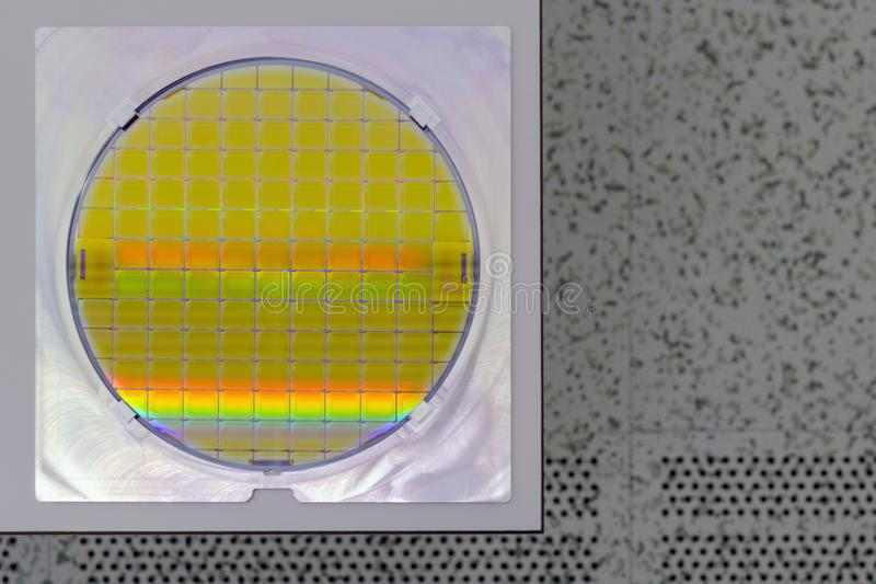 Silicon Wafer in steel holder on a table - A wafer is a thin slice of semiconductor material, such as a crystalline silicon, used. In electronics for the royalty free stock photos