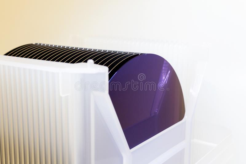 Silicon Wafers in white plastic holder box on a table- A wafer is a thin slice of semiconductor material, such as a crystalline. Silicon Wafers in white plastic royalty free stock photography