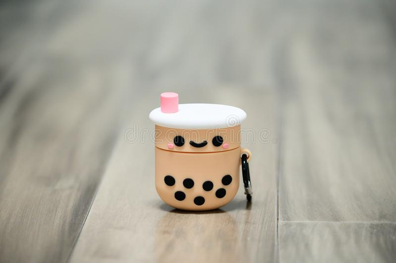 Bubble tea silicone case for Apple Air pod. A silicone case for Apple Air pod on a grey wood floor royalty free stock photography