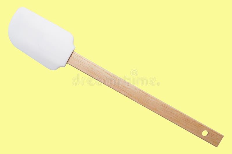 Silicone della spatola della cucina con la maniglia di legno su fondo giallo Isolato fotografie stock libere da diritti