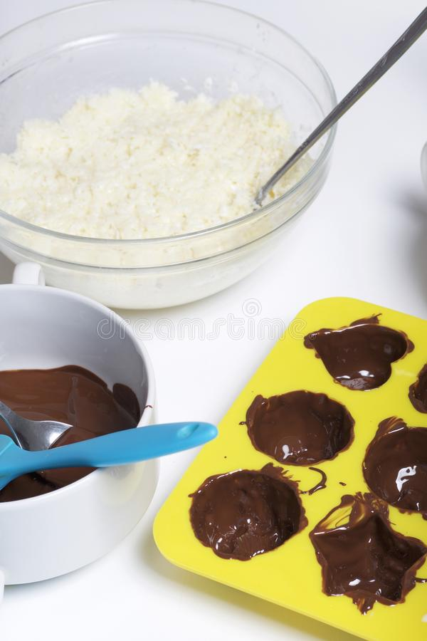 Silicone mold smeared with melted dark chocolate. Ingredients for dessert are on the table. Cooking sweets with coconut and stock photo