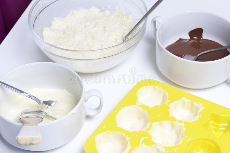 Silicone mold smeared with melted white chocolate. Ingredients for dessert are on the table. Cooking sweets with coconut and royalty free stock photos