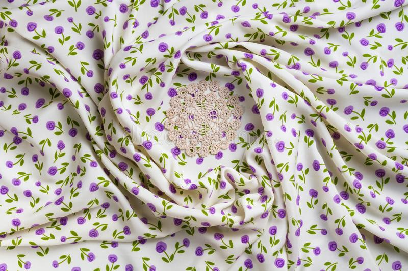Silk fabric tapestry with floral texture and white lace of crochet napkins. In retro style stock photos