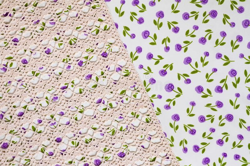 Silk fabric tapestry with floral texture and white lace of crochet napkins. In retro style stock image