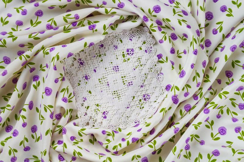 Silk fabric tapestry with floral texture and white lace of crochet napkins. In retro style stock images