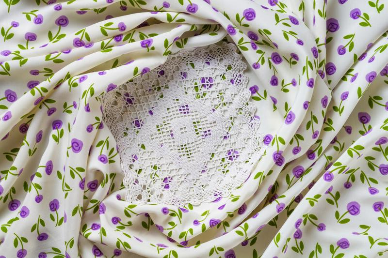 Silk fabric tapestry with floral texture and white lace of crochet napkins. In retro style royalty free stock photography