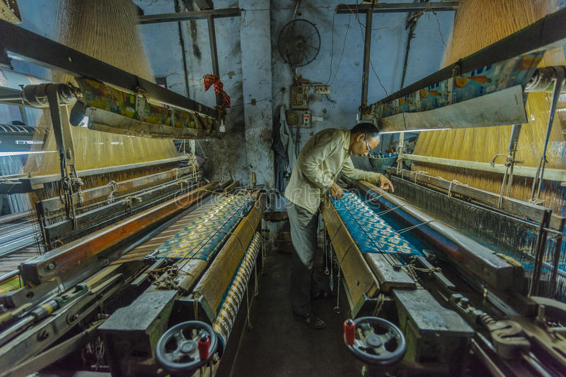 A silk maker examines his work at a small factory in Varanasi, India. A cumbersome machine in a cramped room is the workplace of a silk maker who reviews royalty free stock photos