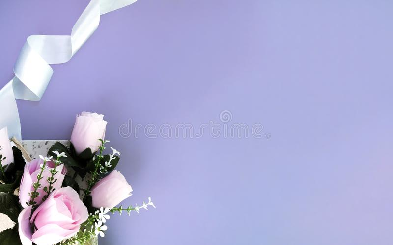 Silk ribbon, pink rose on lilac background. Mothers day, Womens day, Valentines day, birthday or wedding concept. Silk ribbon, pink rose on lilac background stock photo