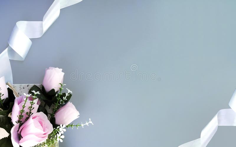 Silk ribbons, pink roses on grey background. Mothers day, Womens day, Valentines day, birthday or wedding concept. Silk ribbons, pink roses on grey background stock image