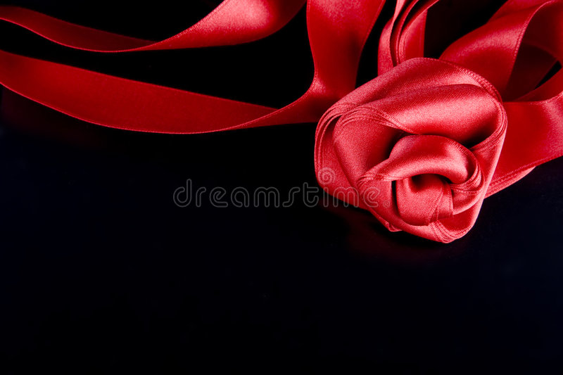 Silk rose. Silk red rose on the black background royalty free stock image