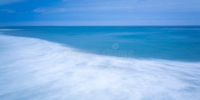 Silkeslent släta blåa havvågor arkivfoton