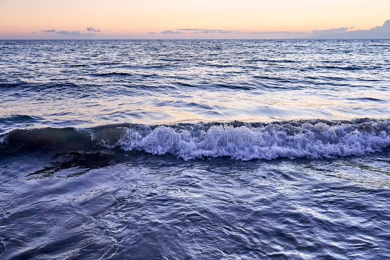 Silky ocean of Hawaii during sunset with waves breaking down on the beach of Maui royalty free stock photography