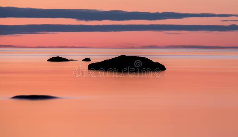 Silky sunset on Lake Vattern, Sweden. A reddish sunset captured on the shore of lake Vattern in Sweden stock photography