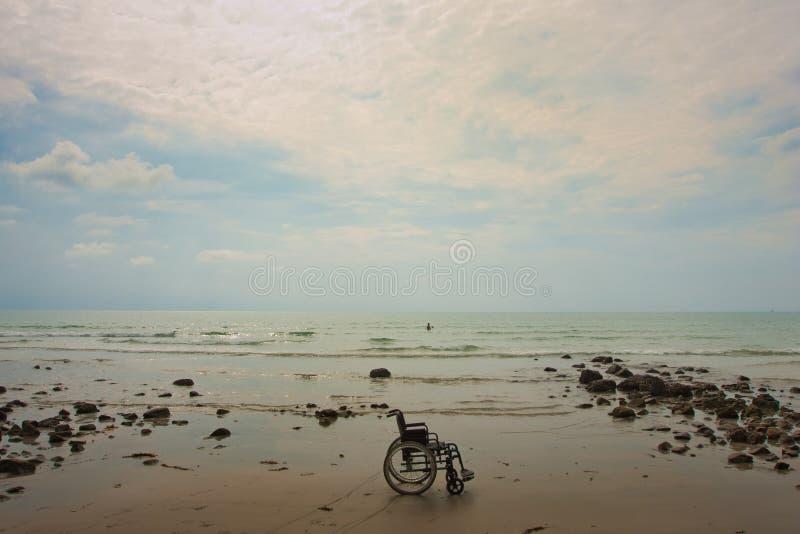 Sillón de ruedas en la playa fotos de archivo libres de regalías
