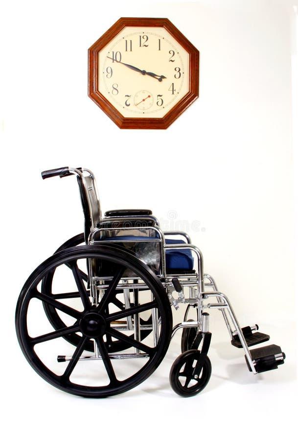 Sillón de ruedas y reloj fotografía de archivo