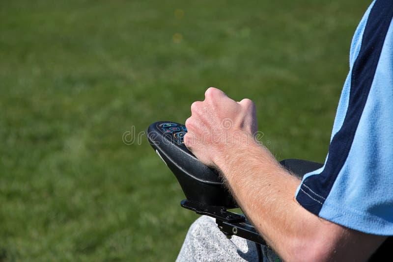 Sill?n de ruedas el?ctrico El hombre joven controla una silla de ruedas con su mano izquierda foto de archivo libre de regalías