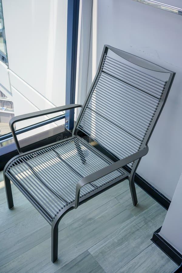 Silla al aire libre moderna negra en terraza de madera fotos de archivo