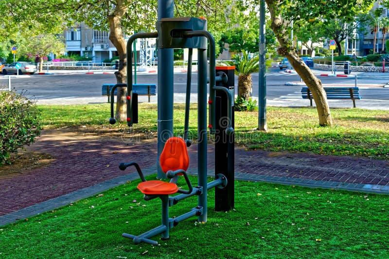 Silla anaranjada del ejercicio público con la estructura gris y las manijas de la ayuda atadas a un polo negro imagen de archivo
