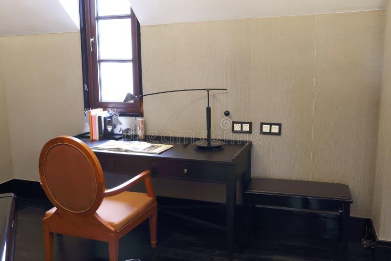 Silla anaranjada, escritorio en la oscuridad del dormitorio del ático foto de archivo libre de regalías