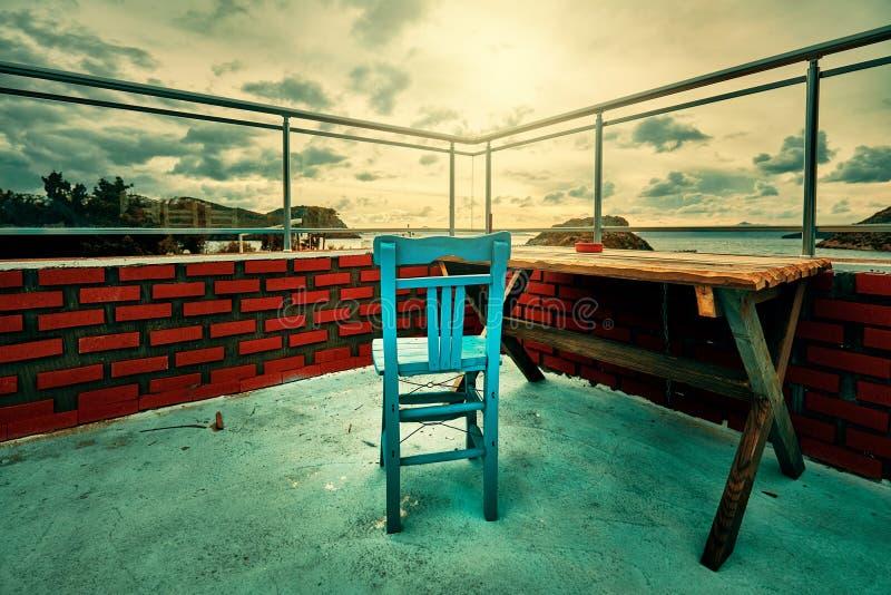 Silla azul de madera retra y una tabla de madera en el balcón con las paredes de ladrillo rojas imagen de archivo
