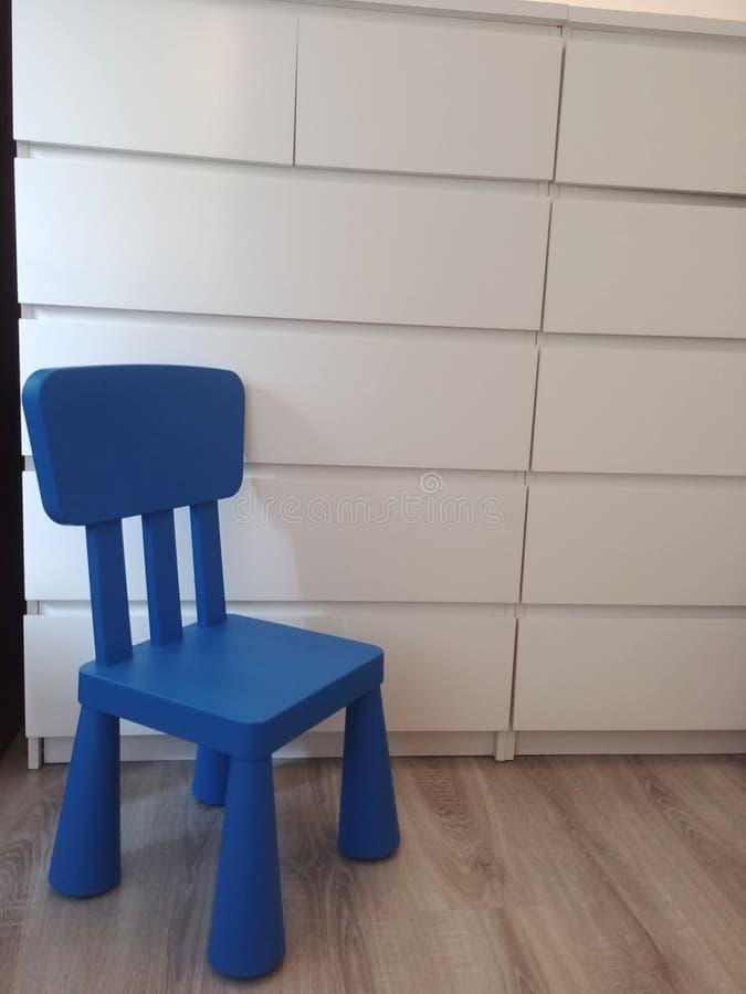 Silla azul del niño plástico fotografía de archivo