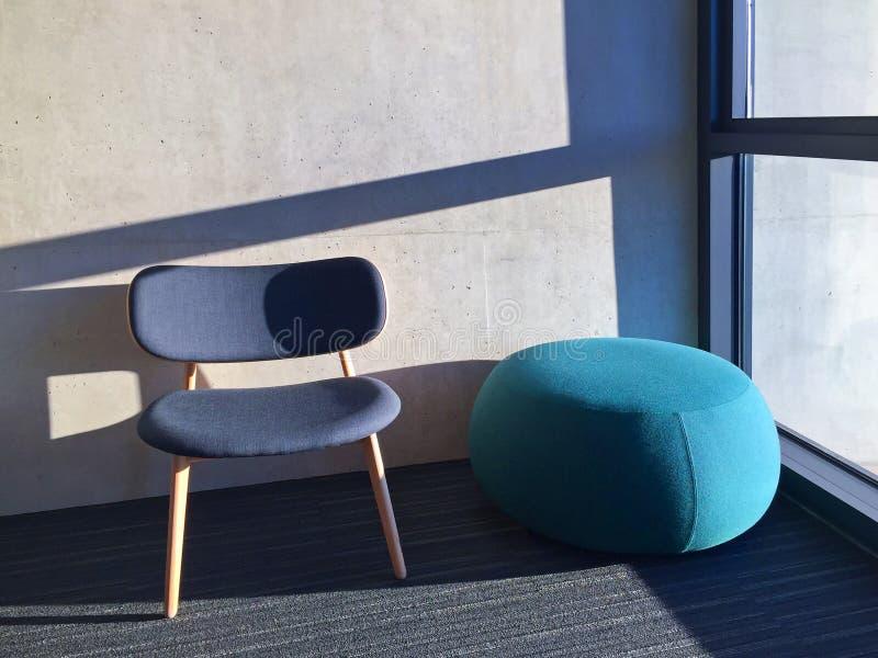 Silla azul en un cuarto con la ventana fotos de archivo libres de regalías