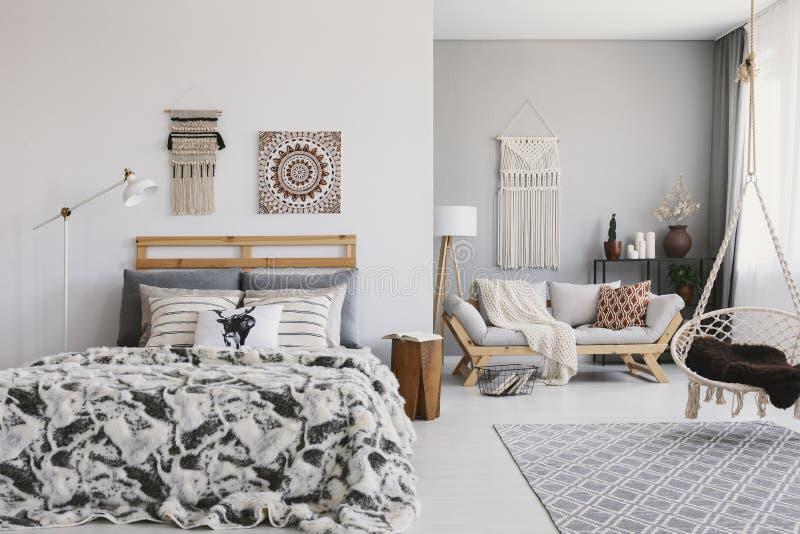 Silla colgante sobre la alfombra en interior espacioso del apartamento del boho con el cartel sobre cama foto de archivo