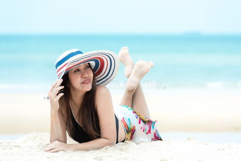 Silla de cubierta en la playa en Brighton Los viajes sonrientes del verano de la moda del bikini de la mujer asiática de la forma foto de archivo