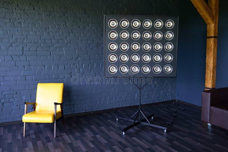 Silla de cuero amarilla cerca de la lámpara pared de ladrillo oscura del negro del desván foto de archivo libre de regalías
