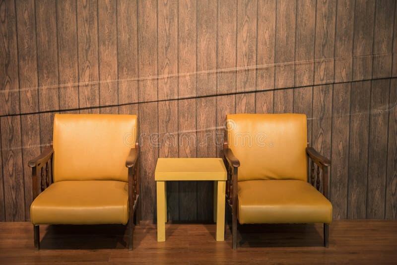 silla de cuero y tabla con la pared de madera imagen de archivo libre de regalías