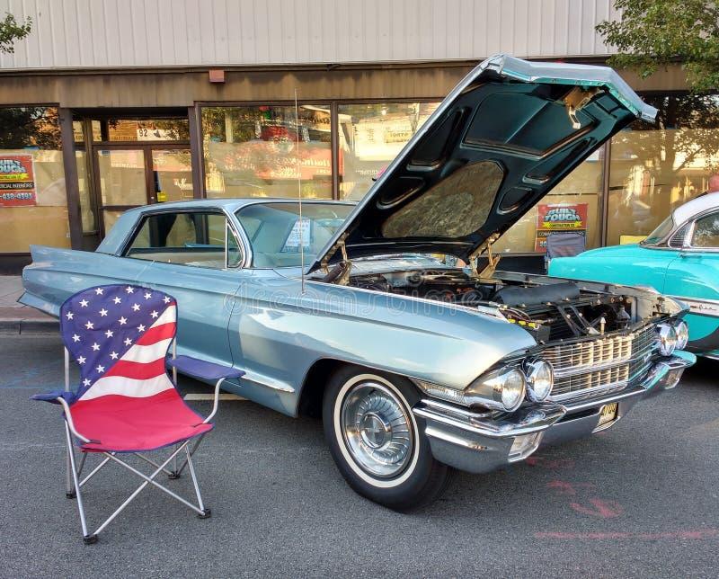 Silla de jardín de la bandera americana cerca de un coche clásico en un Car Show foto de archivo libre de regalías