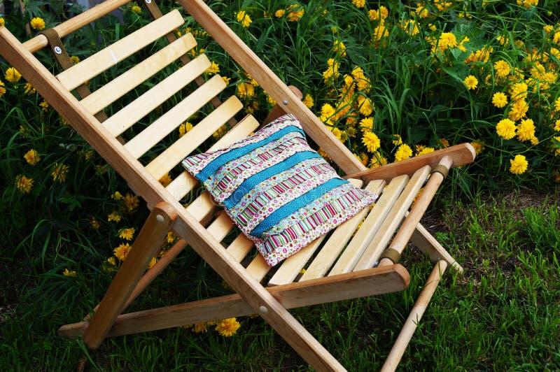 Silla de jardín de madera y almohada hecha en casa de la tela sola imagenes de archivo