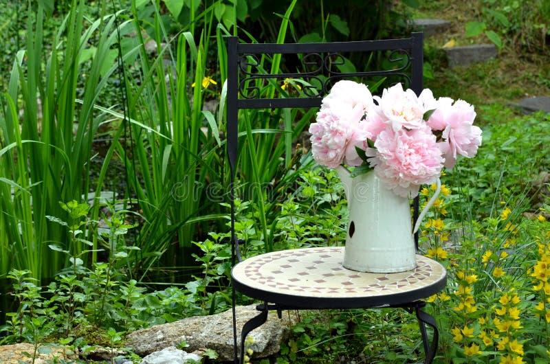 Silla de jardín rosada de los peonies imagenes de archivo
