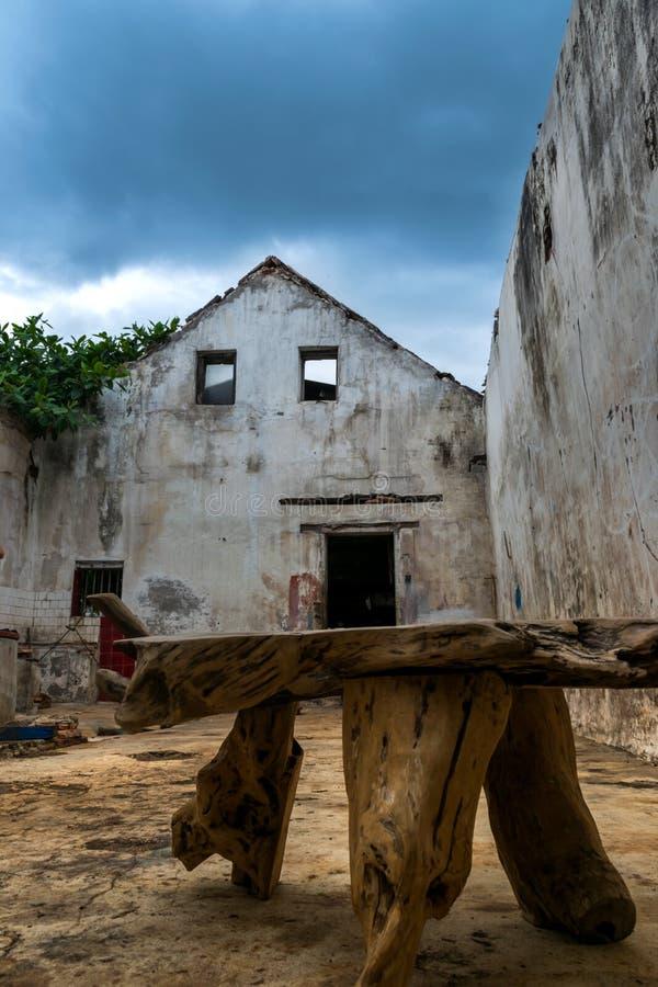 Silla de madera con la pared vieja de la casa como fondo imagen de archivo libre de regalías