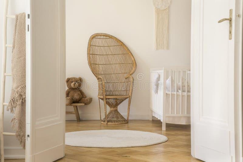 Silla de mimbre del pavo real que se coloca en el interior blanco del sitio del bebé con el pesebre, el oso de peluche y la manta fotos de archivo libres de regalías
