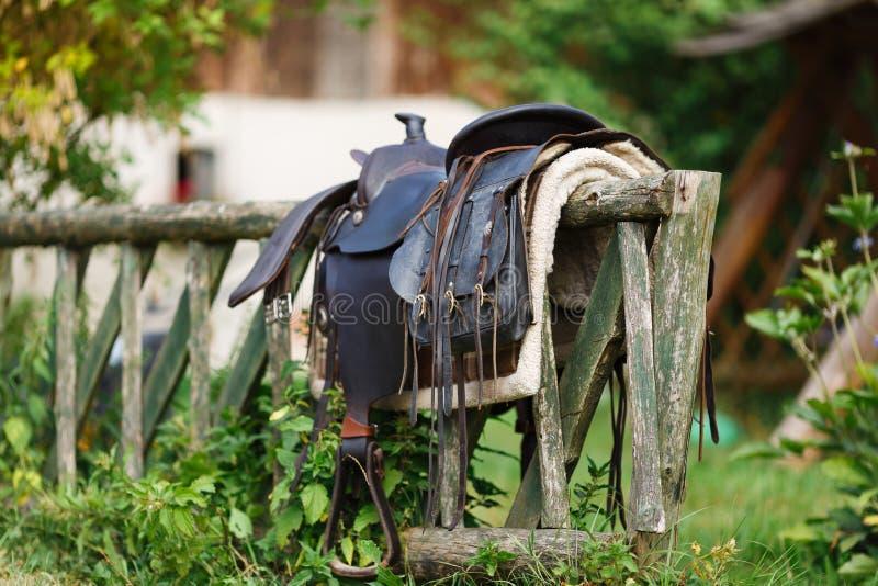 Silla de montar ornamental vieja en la cerca de madera imágenes de archivo libres de regalías