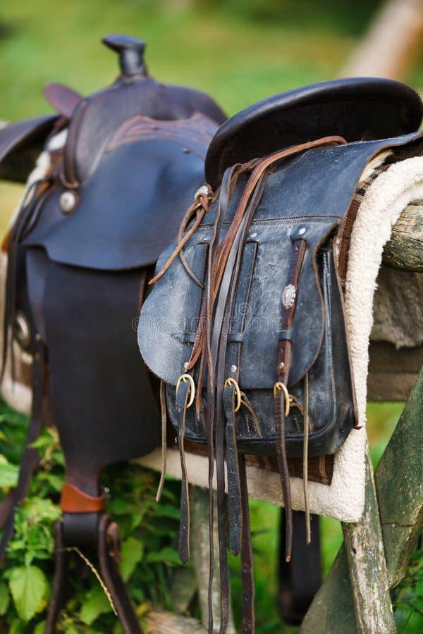 Silla de montar ornamental vieja en la cerca de madera fotografía de archivo