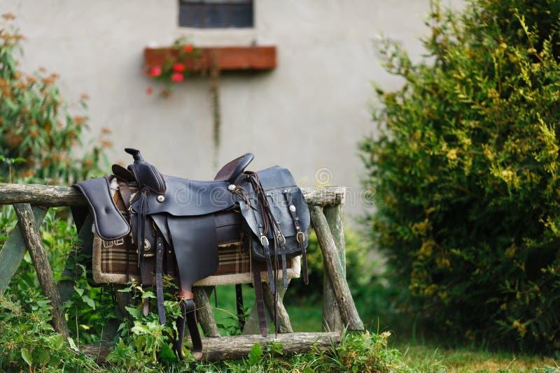 Silla de montar ornamental vieja en la cerca de madera foto de archivo libre de regalías