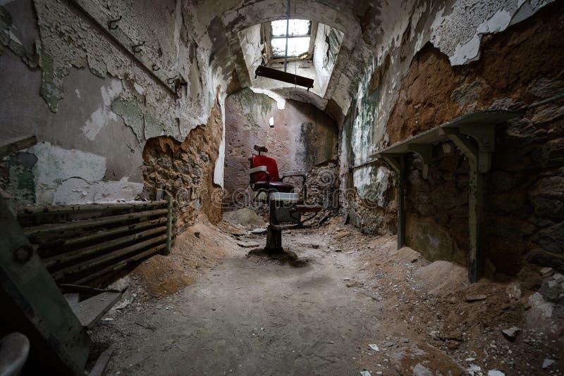 Silla de peluquero roja en una celda de prisión imagen de archivo libre de regalías