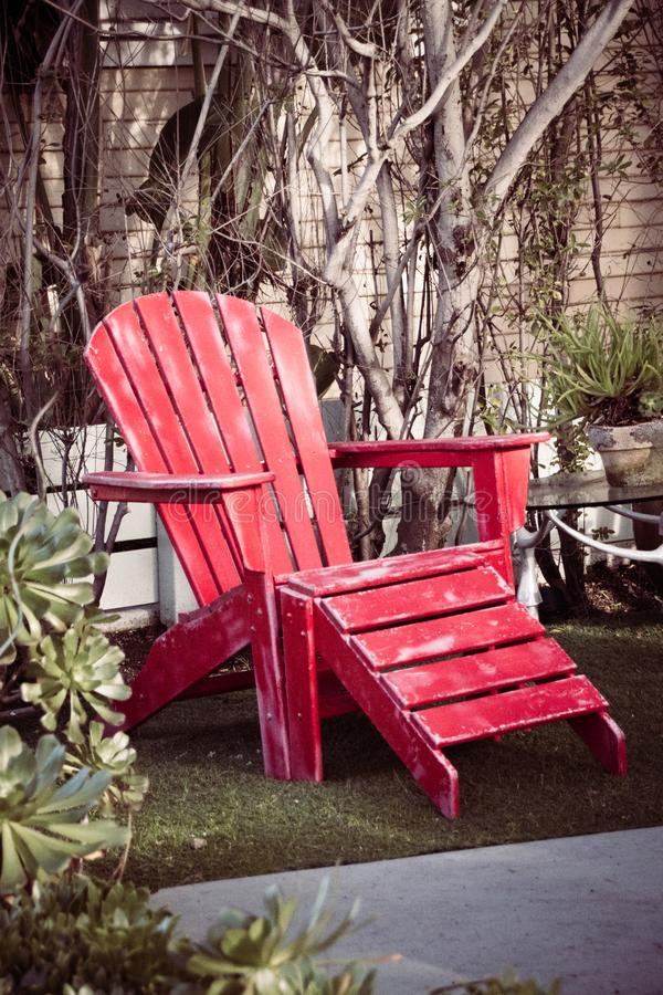 Silla de playa de madera roja del vintage en el jardín fotografía de archivo