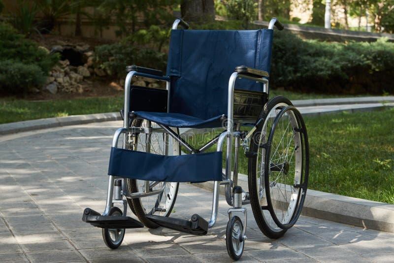 Silla de ruedas vacía en el parque, primer, al aire libre Concepto del milagro foto de archivo