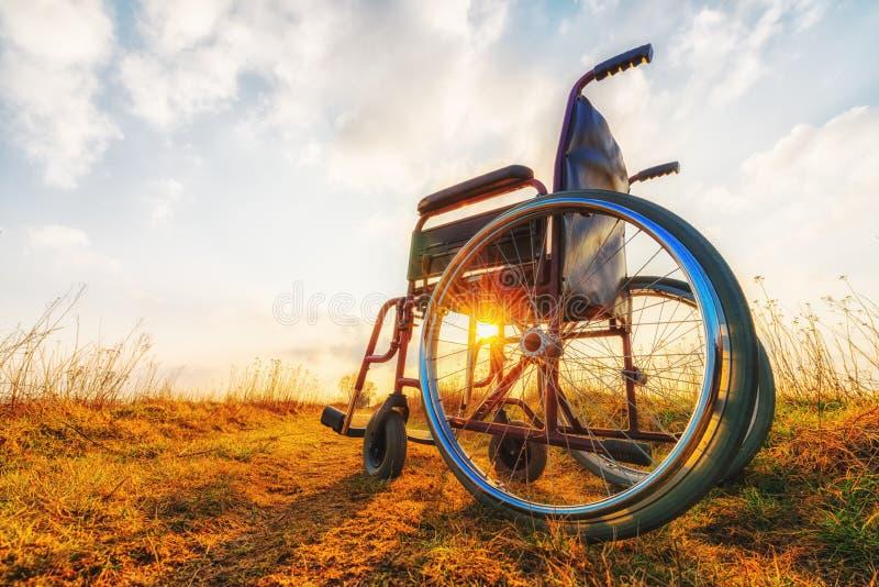 Silla de ruedas vacía en el prado imagen de archivo