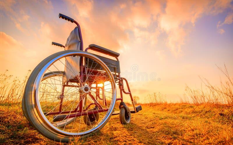 Silla de ruedas vacía en el prado en la puesta del sol