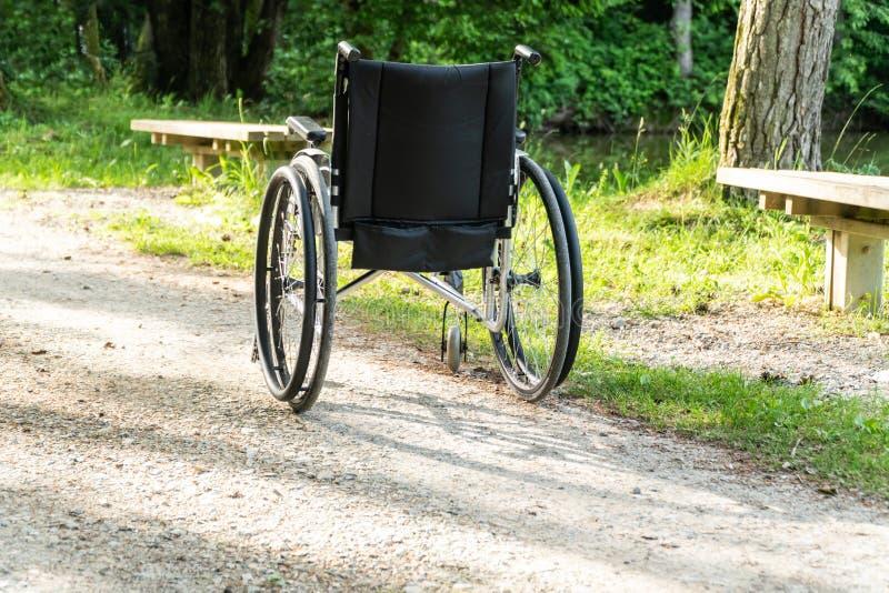 Silla de ruedas vacía parqueada en el parque, concepto de la atención sanitaria fotografía de archivo