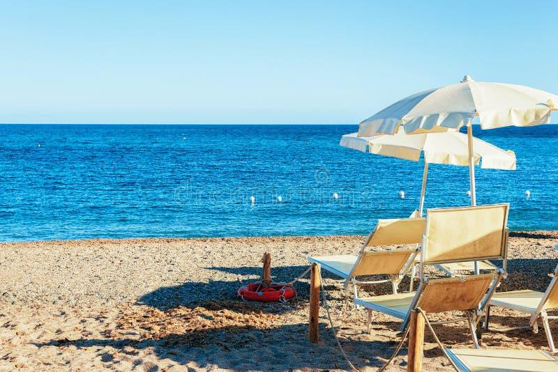 Silla del paraguas y del longue en el mar Mediterráneo de la playa de Chia imágenes de archivo libres de regalías