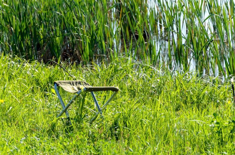 Silla del pescador en la hierba verde fotos de archivo